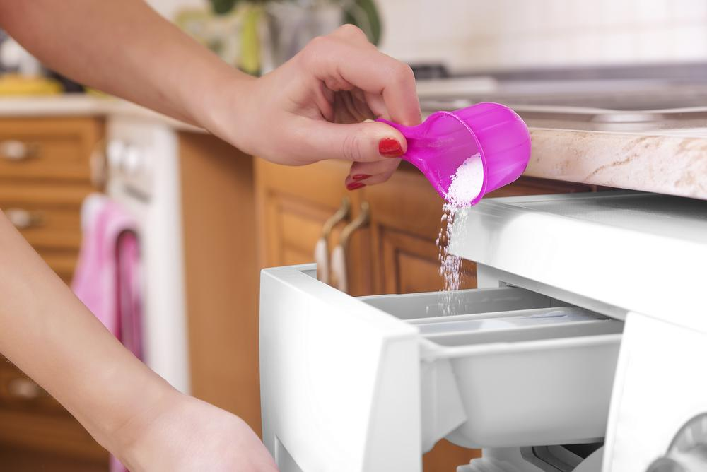 Woman throws laundry detergent powder into the washing machine