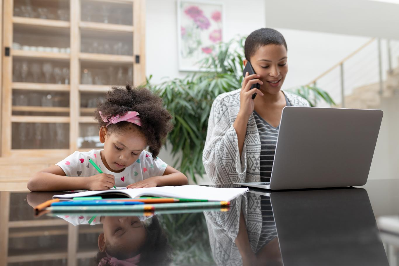 Woman working at home with her daugther